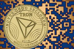 Token trx tron coin cryptocurrency on the background of gold crypto code royalty free stock photography