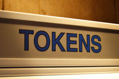Tokens - Sign on Dispensing machine. The sign at the top of the token machine, where money is exchanged for game tokens, at an arcade entertainment center Stock Images