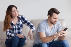Tokig fru som talar till den likgiltiga maken som är upptagen med telefonen royaltyfri foto