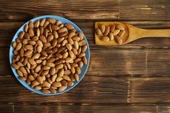 Tokig mandel i en blå platta och spatel på en träyttersida sund mat arkivbild