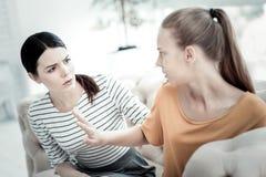 Tokig tonårig flicka som argumenterar med den kvinnliga psykologen Arkivfoto