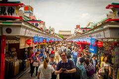 TOKIO, JAPÓN 28 DE JUNIO - 2017: Muchedumbre de gente que mira y que toma imágenes las tiendas en el templo budista Sensoji adent Imagen de archivo libre de regalías