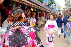 TOKIO, JAPÓN 28 DE JUNIO - 2017: Mujer no identificada que toma una imagen de su amigo en el templo budista Sensoji en Tokio Imagen de archivo libre de regalías