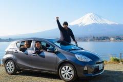 Tokio, Japón - 30 de marzo de 2015: El turista asiático se está sentando en el coche con la montaña de Fuji Fotos de archivo