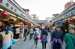 Tokio, Japón - 21 de noviembre de 2013: Dtreet de las compras de Nakamise de la visita de los turistas en Tokio Imágenes de archivo libres de regalías