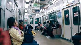 Tokio, Japón - diciembre 5,2016: La gente se sienta en el tren público japonés imagenes de archivo
