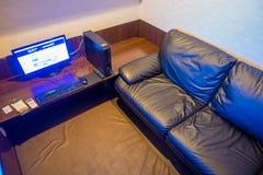 TOKIO, JAPONIA CZERWIEC 28, 2017 -: Inside widok interneta coffe miejsce z komputerem nad drewnianym stołem i czarną kanapą, Obraz Stock