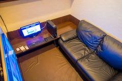 TOKIO, JAPONIA CZERWIEC 28, 2017 -: Inside widok interneta coffe miejsce z komputerem nad drewnianym stołem i czarną kanapą, Zdjęcia Stock