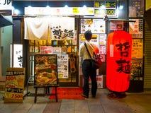 TOKIO, JAPONIA CZERWIEC 28, 2017 -: Niezidentyfikowany mężczyzna sprawdza książe na zewnątrz restauraci w Shinjuku Złotym i menu Fotografia Royalty Free