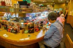 TOKIO, JAPONIA -28 2017 JUN: Niezidentyfikowani ludzie je asortowanego japanesse jedzenie nad stołem wśrodku kaitenzushi, Fotografia Royalty Free
