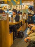 TOKIO, JAPONIA -28 2017 JUN: Niezidentyfikowani ludzie je asortowanego japanesse jedzenie nad stołem wśrodku kaitenzushi, Obrazy Stock