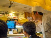 TOKIO, JAPONIA -28 2017 JUN: Niezidentyfikowani ludzie je asortowanego japanesse jedzenie nad stołem wśrodku kaitenzushi, Obrazy Royalty Free