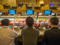 TOKIO, JAPONIA -28 2017 JUN: Niezidentyfikowani ludzie je asortowanego japanesse jedzenie nad stołem wśrodku kaitenzushi, Fotografia Stock