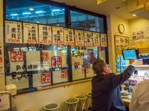 TOKIO, JAPONIA -28 2017 JUN: Niezidentyfikowani ludzie je asortowanego japanesse jedzenie nad stołem wśrodku kaitenzushi, Zdjęcie Royalty Free
