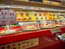 TOKIO, JAPONIA -28 2017 JUN: Widok asortowany japanesse jedzenie nad stołem wśrodku kaitenzushi konwejeru paska suszi, Obraz Royalty Free