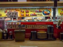 TOKIO, JAPONIA -28 2017 JUN: Widok asortowany japanesse jedzenie nad stołem wśrodku kaitenzushi konwejeru paska suszi, Obrazy Royalty Free