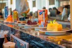 TOKIO, JAPONIA -28 2017 JUN: Zamyka up asortowany japanesse jedzenie nad stołem wśrodku kaitenzushi konwejeru paska suszi, Obrazy Royalty Free