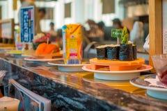 TOKIO, JAPONIA -28 2017 JUN: Zamyka up asortowany japanesse jedzenie nad stołem wśrodku kaitenzushi konwejeru paska suszi, Fotografia Stock