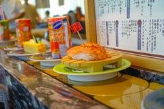 TOKIO, JAPONIA -28 2017 JUN: Zamyka up asortowany japanesse jedzenie nad stołem wśrodku kaitenzushi konwejeru paska suszi, Fotografia Royalty Free