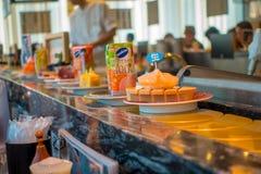 TOKIO, JAPONIA -28 2017 JUN: Zamyka up asortowany japanesse jedzenie nad stołem wśrodku kaitenzushi konwejeru paska suszi, Zdjęcie Royalty Free