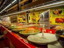 TOKIO, JAPONIA -28 2017 JUN: Zamyka up asortowany japanesse jedzenie nad stołem wśrodku kaitenzushi konwejeru paska suszi, Obraz Royalty Free