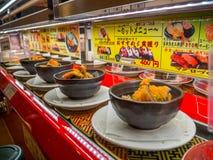 TOKIO, JAPONIA -28 2017 JUN: Zamyka up asortowany japanesse jedzenie nad stołem wśrodku kaitenzushi konwejeru paska suszi, Zdjęcia Royalty Free