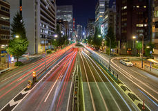 Tokyo Avenue at night. Tokyo, Japan - September 5, 2016: Car light trails in a busy wide avenue with a tunnel in the middle and illuminated buildings on the Royalty Free Stock Image