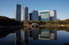 Tokyo city business buildings and garden. Hama-rikyu Gardens, Tokyo city business buildings, impressive modern architectural lines and reflections against the Royalty Free Stock Photo