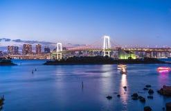 Tokyo fjärd och regnbågebro under skymning royaltyfri fotografi