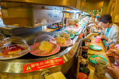 TOKYO, GIAPPONE -28 GIUGNO 2017: Gente non identificata che mangia un alimento assortito del japanesse sopra una tavola, dentro d Fotografia Stock