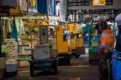 TOKYO, GIAPPONE 28 GIUGNO - 2017: Lavoratori non identificati con una piccola macchina di giallo del carico, dentro di un mercato Immagini Stock Libere da Diritti