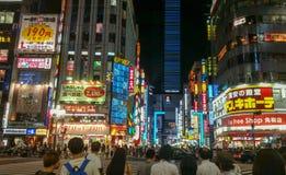 Tokyo, GIAPPONE, l'8 agosto 2017: Le insegne al neon illuminano la vicinanza occupata di Shinjuku alla notte Immagini Stock