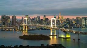 Tokyo horisont med det Tokyo tornet och regnbågebron Arkivfoton