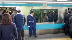 TOKYO, JAPAN - APRIL, 18, 2018: commuters at train station and platform guard in tokyo