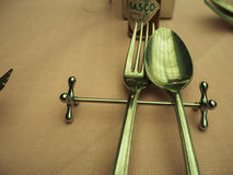 Tokyo, Japan - April 4, 2016: Spoon and fork on metal rest with. Part of Tabasco sauce bottle on dining table with light pink paper table cloth Royalty Free Stock Image