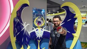 Happy tourist posing infront of a Pokemon figure at Pokemon Center store in Sunshine City shopping mall in Tokyo, Japan. Tokyo, Japan - August 2018: Happy royalty free stock photo