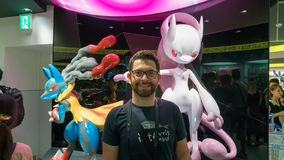 Happy tourist posing infront of a Pokemon figure at Pokemon Center store in Sunshine City shopping mall in Tokyo, Japan. Tokyo, Japan - August 2018: Happy stock photo