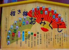 Tokyo, Japan - 24. August 2017: Informatives Zeichen eines japanesse Buchstaben in einem Holztisch mit einigen Animekatzen, in To Lizenzfreie Stockfotografie