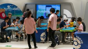 Parents with their children playing Pokemon arcade video games at Pokemon Center, Sunshine City Mall, Tokyo, Japan. Tokyo, Japan - August 2018: Parents with royalty free stock photos