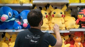 Unidentified man looking at plush Pokemon toys at the Pokemon Center store located in Sunshine City mall, Tokyo, Japan. Tokyo, Japan - August 2018: Unidentified royalty free stock photography