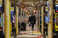 Woman walking and Japanese people playing in a Pachinko parlor of Shinjuku district royalty free stock photo