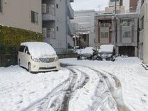 Tokyo, Japan - 9. Februar 2014: Schneebedeckungsautos parkten nach Blizzard in Tokyo Stockfotografie