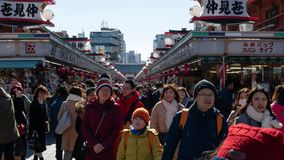 Crowds of tourists and locals walk and shop along Nakamise Dori shopping street by Sensoji shrine in Asakusa district of Tokyo, stock image