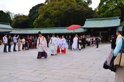 A line of people walking into a shrine in a wedding ceremony. stock images