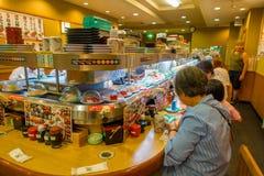 TOKYO, JAPAN -28 IM JUNI 2017: Nicht identifizierte Leute, die ein sortiertes japanesse Lebensmittel über einer Tabelle, innerhal Lizenzfreies Stockbild