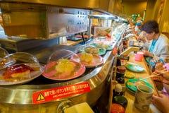 TOKYO, JAPAN -28 IM JUNI 2017: Nicht identifizierte Leute, die ein sortiertes japanesse Lebensmittel über einer Tabelle, innerhal Stockfoto