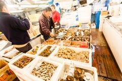 Tokyo Japan - Januari 15, 2010: De första kunderna köper den nya fisken på ottan i Tsukiji fiskmarknad royaltyfria bilder