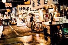Tokyo, Japan - Januari 15, 2010: Vroege ochtend in Tsukiji-Vissenmarkt Arbeider die verse vissen en zeevruchten op de teller opma stock foto