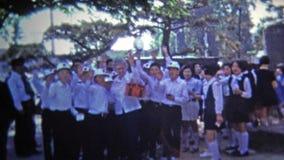 TOKYO, JAPAN -1972: Japanse schooljongens die vaarwel aan deviezenleraar golven stock footage