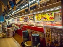 TOKYO, JAPAN -28 JUN 2017: Mening van geassorteerd japanesse voedsel over een lijst, binnen van een sushi van de kaitenzushitrans Stock Afbeeldingen